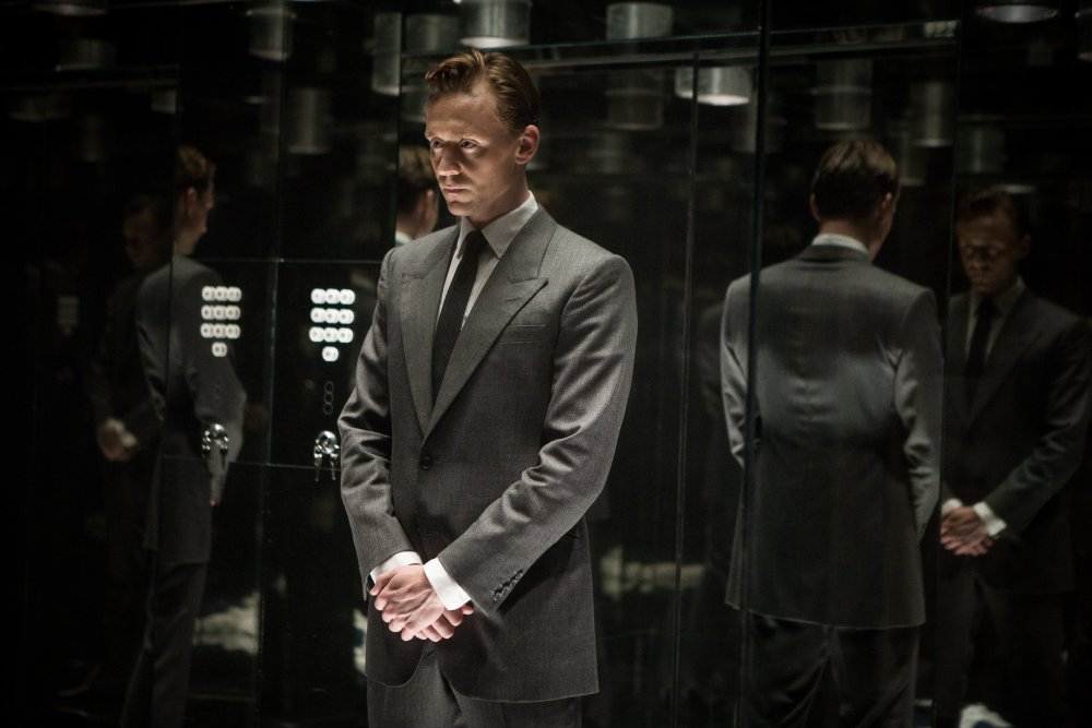 high-rise-2015-001-tom-hiddleston-standing-black-walls