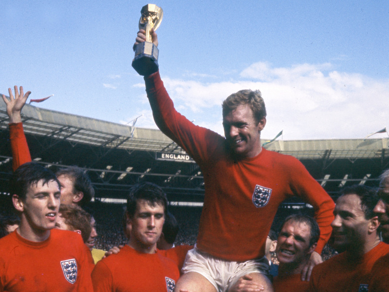 30 July 1966 - FIFA World Cup Final - England v West Germany - Bobby Moore holds the JUles Rimet trophy and is hoisted on the shoulders of Ray Wilson (right) and Geoff Hurst, with Martin Peters far left.Photo: Gerry Cranham / Offside.